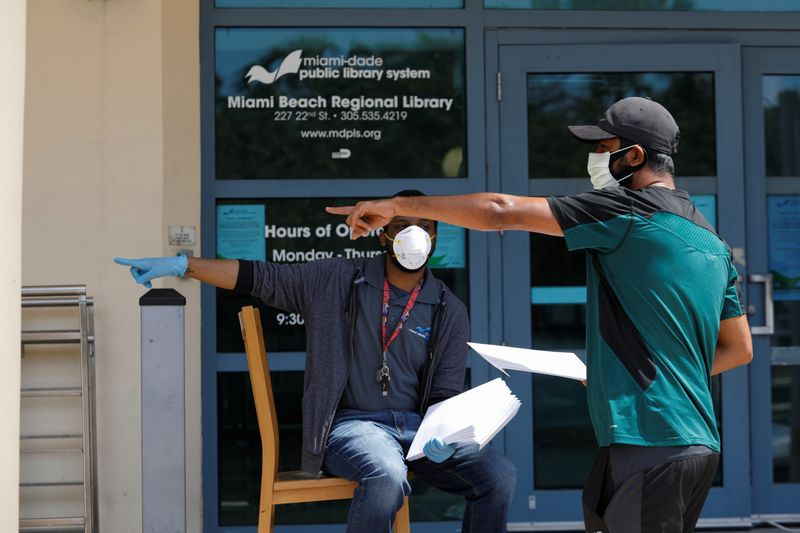 A man speaks with a library worker after receiving an unemployment form, as the outbreak of coronavirus disease (COVID-19) continues, in Miami Beach